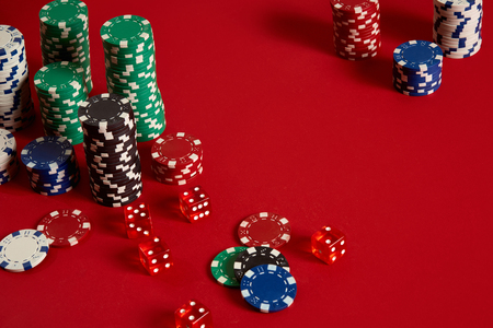 Poker chips on red background. Group of different poker chips. Casino background. Stock Photo