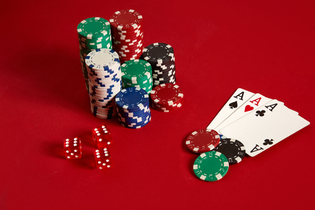 Casino gambling poker equipment and entertainment concept - close up of playing cards and chips at red background. Three of a Kind