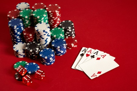 Casino gambling poker equipment and entertainment concept - close up of playing cards and chips at red background. Four of a Kind