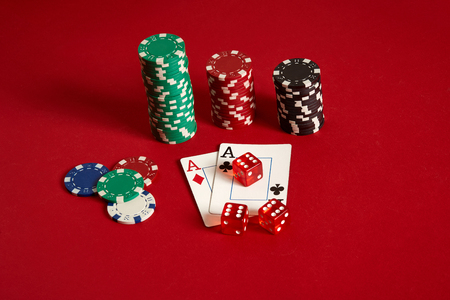 Poker chips and aces on red background. Group of different poker chips. Casino background.