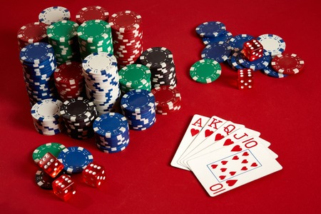 Casino gambling poker equipment and entertainment concept - close up of playing cards and chips at red background. Royal flush heart.