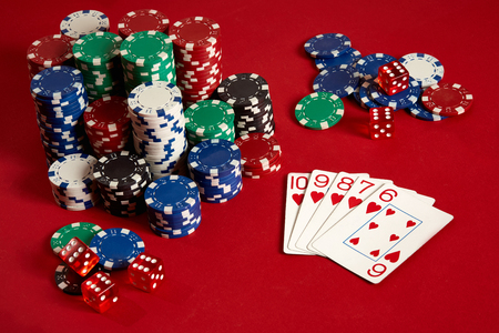 Casino gambling poker equipment and entertainment concept - close up of playing cards and chips at red background. Straight Flush