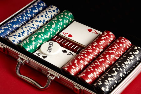 Poker set in metal suitcase. Risky entertainment of gambling. Top view on red background