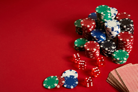 Poker chips and Card deck on red background. Group of different poker chips. Casino background.
