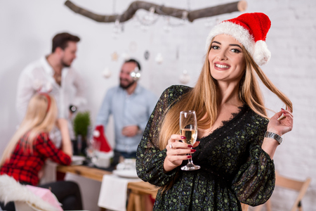 Portrait of a young woman with a glass of champagne at home on the foreground. Beautiful blonde in a Santa hat and black dress Фото со стока
