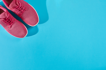 New pink sneakers on blue background with copy space. Sport concept