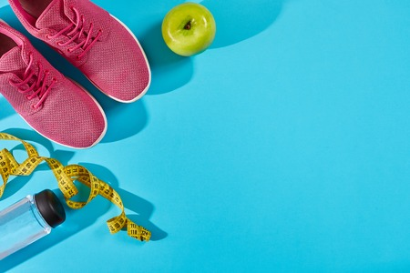 Sneakers with measuring tape on cyan blue background. Centimeter in yellow color near pink trainers, close up.