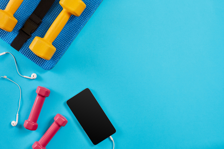 Dumbbells and mobile phone on blue background. Top view. Fitness, sport and healthy lifestyle concept.