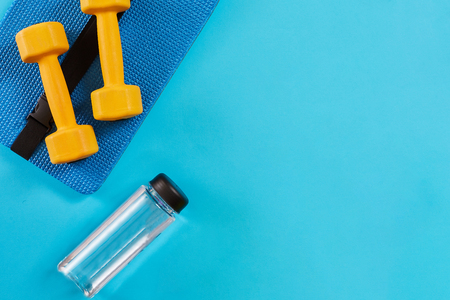 Dumbbells and bottle of water on blue background. Top view. Fitness, sport and healthy lifestyle concept.