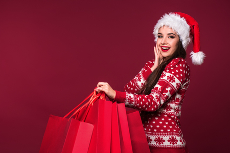 Young pretty woman or girl with long beautiful hair in Santa hat and New Years dress holding red package on red studio background