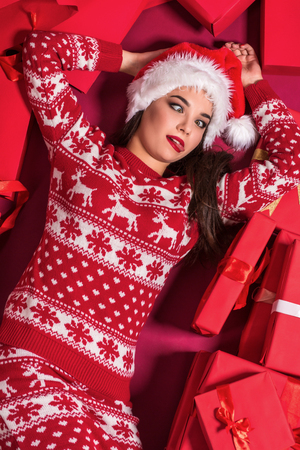 Funny young woman in a New Years dress lying on a mountain of gifts. Stock Photo