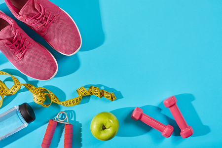Sneakers with measuring tape on cyan blue background. Sport shoes and sportive equipment for healthy shape. Stock Photo
