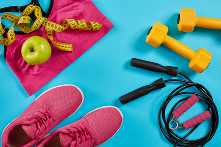 Athletes set with female clothing, dumbbells and bottle of water on bright blue background