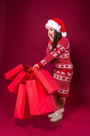 Attractive woman is holding many packages of bought presents with both her hands. Young woman is standing and laughing.