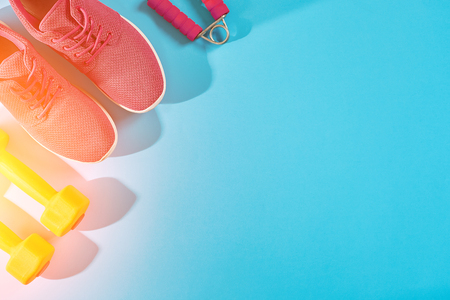 Female sport shoes and equipment top view, copy space. Active lifestyle, body care concept. Sun flare