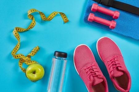 シアンブルーの背景に測定テープ付きスニーカー。黄色のセンチメートル、ピンクのスニーカー、ダンベルと水のボトル、コピースペース。