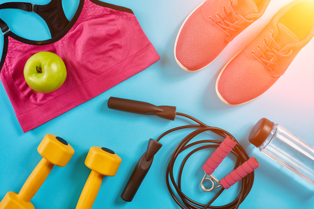 Athletes set with female clothing, dumbbells and bottle of water on bright blue background. Sun flare