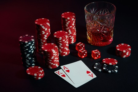 Cards of poker player. On the table are chips and a glass of cocktail with whiskey. Cards - Ace and King