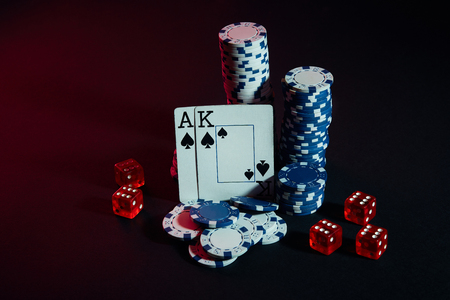 Stack of chips and two cards on dark background - poker game concept