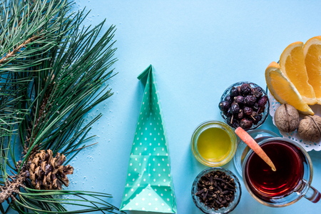 Hot mulled wine with orange, anise, cardamon and cinnamon on blue background. Christmas tree branches, gifts and cones.