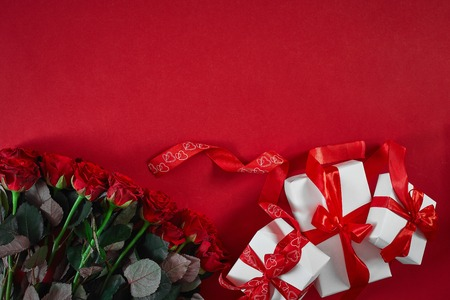 Top view fresh red rose flower and gift box on red deck with empty space for design. For love or valentine day concept