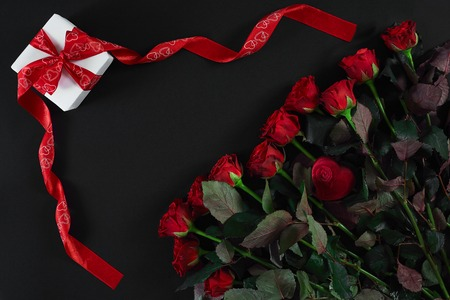 Red roses and gift box on black background Stock Photo