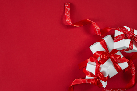 White gift boxes with red ribbon on red background. Valentines d