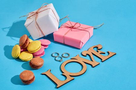 Macaroons and gift boxes on a blue background with the words love