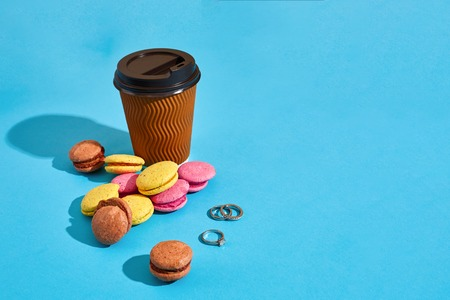 Hot coffee in brown paper cup with black lid and macaroons on bl