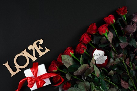 Red roses, ring and gift box on black background Stock Photo