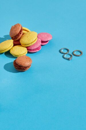 Colorful macaroons. Wedding rings. Marriage proposal. The concept of Valentines Day