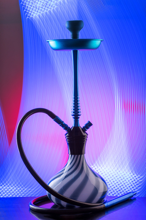 Blue hookah with black rubber tube and blue and white flask on interesting colorful background. Stock Photo