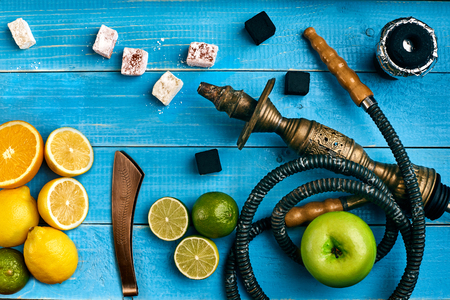 Arabic hookah with a tobacco flavor of a mixture of citruses and apple. Top view of a blue wooden background. Still life. Copy space. Flat lay