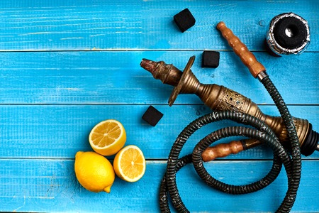 Tobacco background. Turkish smoking hookah with tobacco flavor of ripe lemon. Top view of a blue wooden background. Still life. Copy space. Flat lay Stock Photo