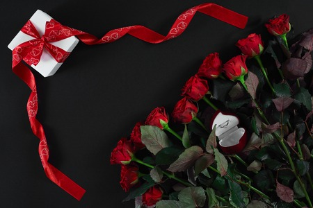Red roses, ring and gift box on black background. Top view. Flat lay. Copy space. Still life