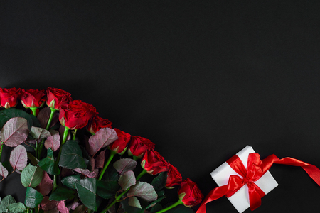 Red roses and white gift box with red ribbon on black background. Top view. Flat lay. Copy space. Still life