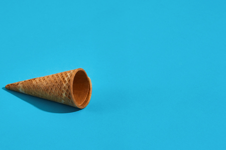 Waffle ice cream cones with shadow on a blue background. Still life. Copy space Stock Photo