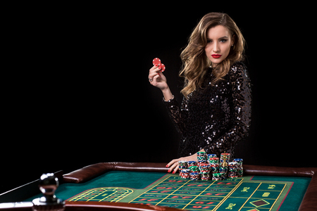 Woman playing in casino. Woman stakes piles of chips playing rou Archivio Fotografico
