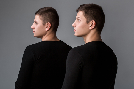 The two twin brother stand with their backs on the gray backgrou