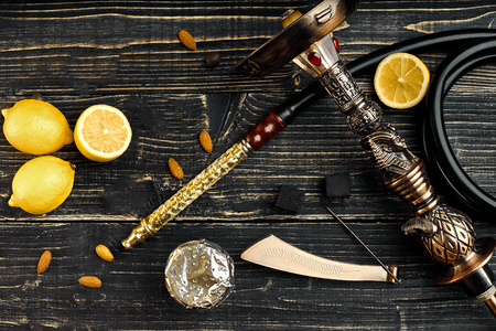 Dismantled parts of hookah on a wooden background with lemon fruit. Top view. Flat lay. Copy space. Still life