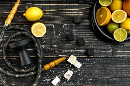 Stylish Smoking hookah and basket with lemon, lime and orange on wooden background. Top view. Flat lay. Copy space. Still life Stock Photo