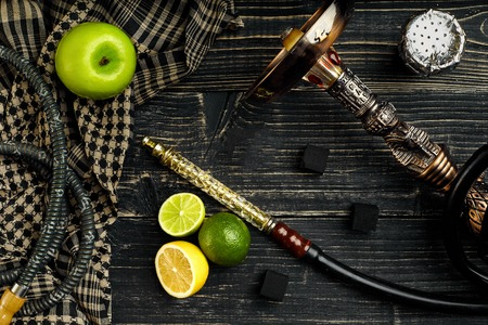 Dismantled parts of hookah on a wooden background with lime and apple fruits. Top view. Flat lay. Copy space. Still life Stock Photo