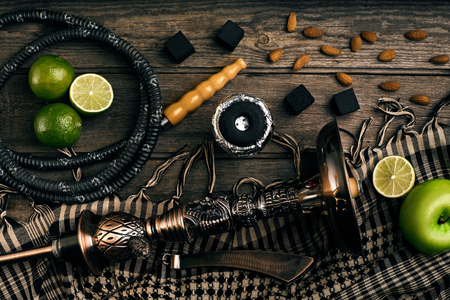 Dismantled parts of hookah on a wooden background with lime fruit. Top view. Flat lay. Copy space. Still life