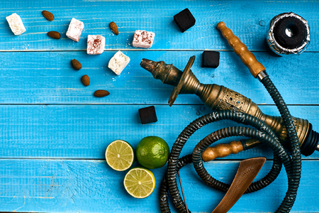 Tobacco background. Turkish smoking hookah with tobacco flavor of ripe lime. Top view of a blue wooden background. Still life. Copy space. Flat lay
