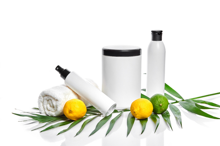 White bottles and two whole lemon and lime isolated on white background. The concept for advertising cosmetics