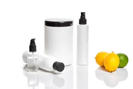 White bottles and two whole lemon and lime isolated on white background. The concept for advertising cosmetics. Still life. Copy space