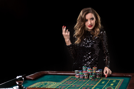 Woman playing in casino. Woman stakes piles of chips playing rou Banco de Imagens
