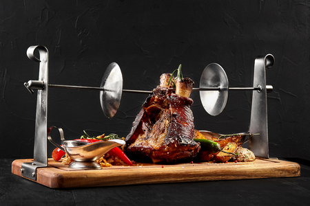 Roasted pork knuckle eisbein with braised boiled cabbage, potatoes, chili peppers and mustard on wooden cutting board, on a black background. Serving a ready meal in a restaurant, cafe, bar, pub. Still life. Copy space