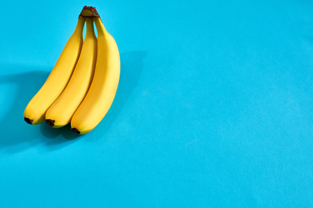 Yellow ripe bananas on blue background with space for text or design. Top view Stock Photo