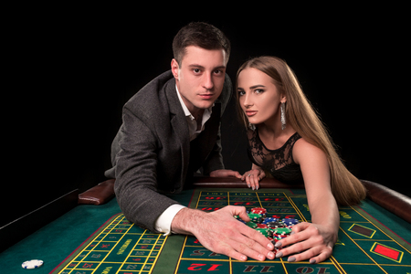 Young beautiful couple takes their winnings at the roulette table at the casino